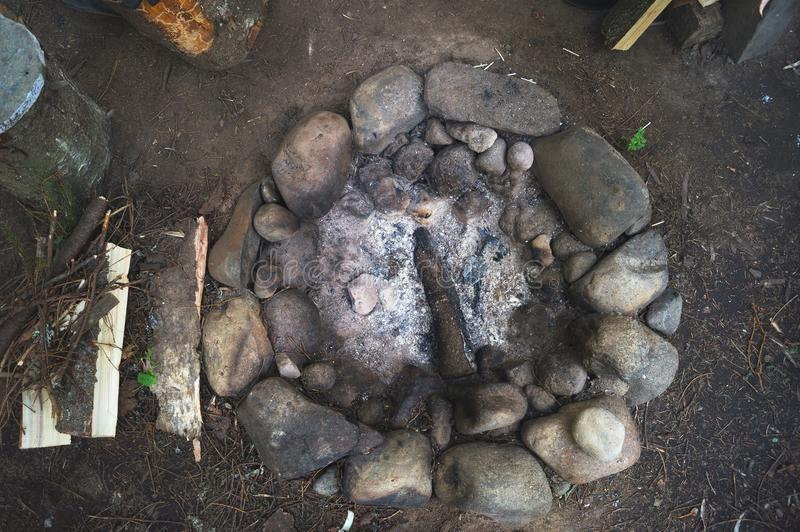 Στρογγυλή δασική εστία πετρών με τον άνθρακα και την ξύλινη τέφρα Στρατόπεδο δασικών στάσεων των κυνηγών και των τουριστών στοκ εικόνες
