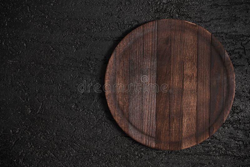 Στρογγυλός ξύλινος τέμνων πίνακας στο μαύρο πίνακα Τοπ άποψη του κενού καθιερώνοντος τη μόδα αγροτικού ξύλινου δίσκου κουζινών στοκ εικόνα
