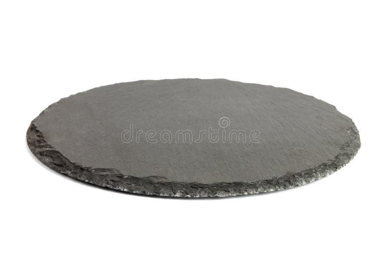 Στρογγυλό αγροτικό μαύρο πιάτο πετρών πλακών, που απομονώνεται στο άσπρο υπόβαθρο στοκ φωτογραφία