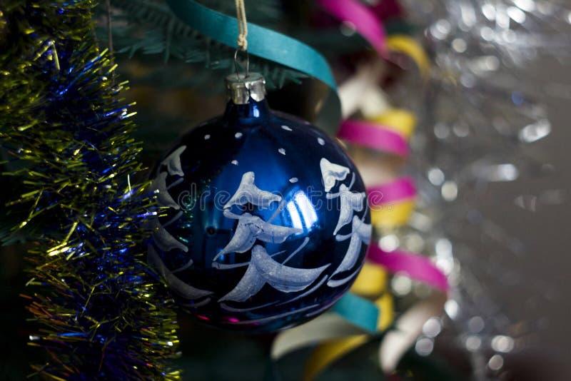 Στρογγυλό κρεμώντας παιχνίδι Χριστουγέννων που διακοσμείται με τις γιρλάντες στο υπόβαθρο δέντρων στοκ φωτογραφία