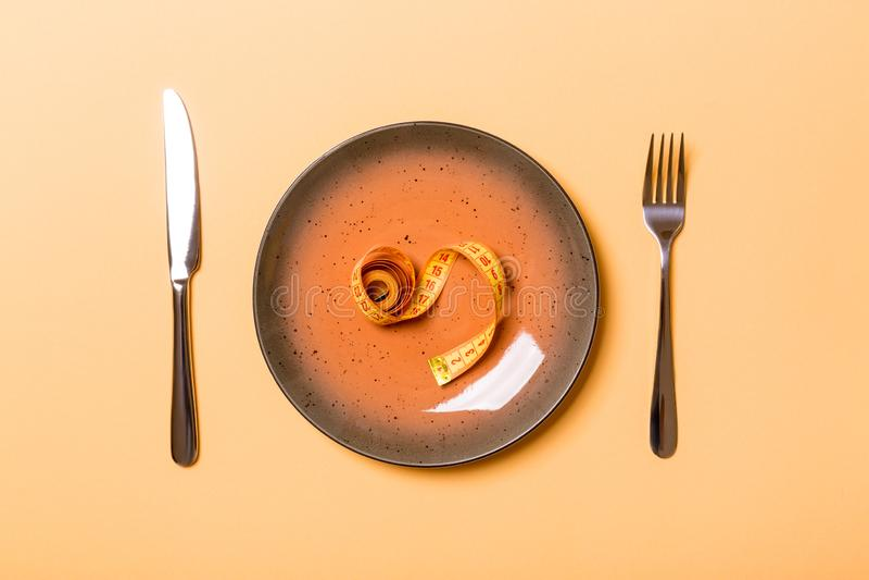 Στρογγυλό πιάτο με την ταινία μέτρου μέσα με το δίκρανο και το μαχαίρι στο πορτοκαλί υπόβαθρο Τοπ άποψη της έννοιας παχυσαρκίας στοκ εικόνες