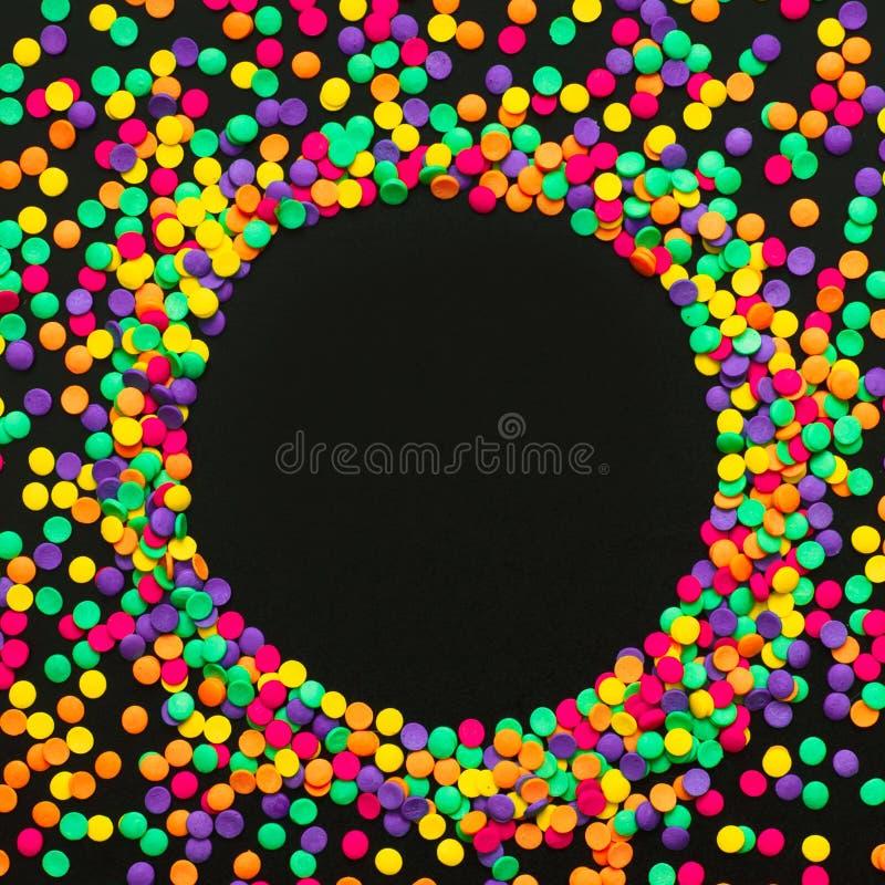 Στρογγυλό πλαίσιο του πολύχρωμου κομφετί στο μαύρο υπόβαθρο στοκ εικόνα με δικαίωμα ελεύθερης χρήσης