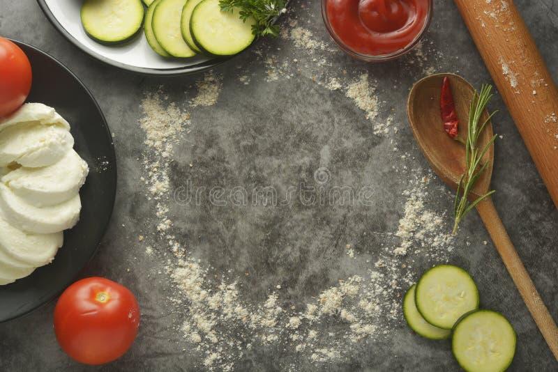 Στρογγυλό πλαίσιο φιαγμένο από αλεύρι, κυλώντας καρφίτσα και λαχανικά - zuchinni, ντομάτες, κέτσαπ, μοτσαρέλα στο γκρίζο υπόβαθρο στοκ φωτογραφίες με δικαίωμα ελεύθερης χρήσης