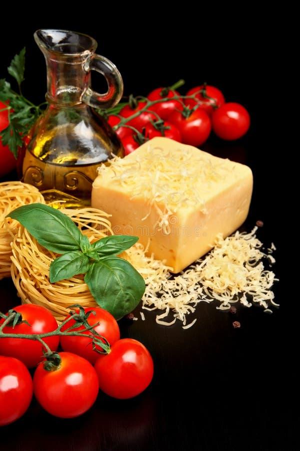 Στρογγυλές σφαίρες των ζυμαρικών με το τυρί, ντομάτες, βασιλικός, ελαιόλαδο στο Μαύρο στοκ εικόνες με δικαίωμα ελεύθερης χρήσης