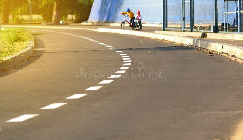 Στροφή της ασφαλτωμένης πορείας ποδηλάτων στο πάρκο για τις αθλητικές δραστηριότητες αναμμένο από τις ακτίνες του ήλιου στοκ φωτογραφίες με δικαίωμα ελεύθερης χρήσης