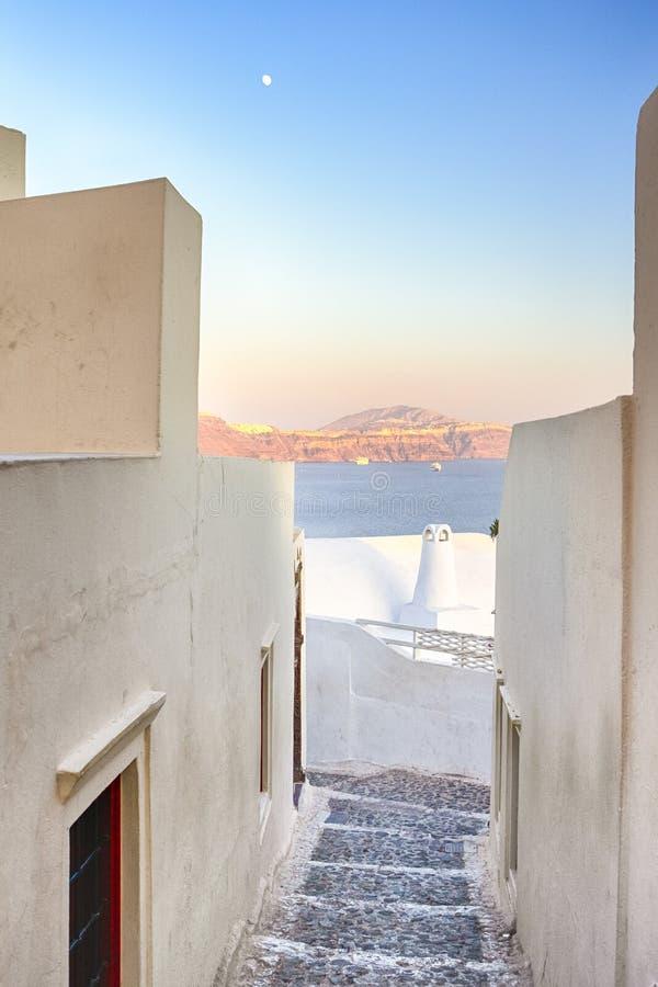 Στρωμένα σκαλοπάτια Oia του χωριού στο νησί Santorini με ηφαιστειακό Caldera και του φεγγαριού στο υπόβαθρο στοκ φωτογραφία