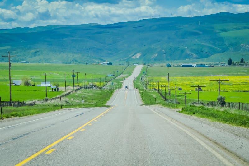 Στρωμένος δρόμος στο εθνικό πάρκο Yellowstone, Ουαϊόμινγκ, Ηνωμένες Πολιτείες, μεταξύ των λιβαδιών, των βουνών και του νεφελώδους στοκ φωτογραφίες