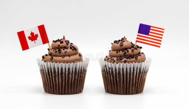 Στρόβιλος τσιπ σοκολάτας δύο cupcakes με τη αμερικανική σημαία tricolor και τις καναδικές οδοντογλυφίδες σημαιών φύλλων σφενδάμου στοκ εικόνες με δικαίωμα ελεύθερης χρήσης