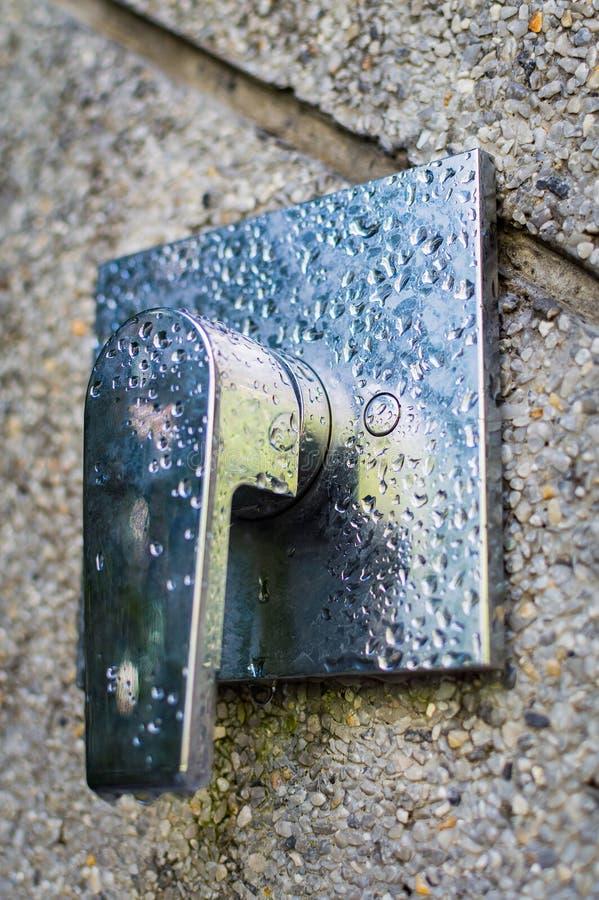Στρόφιγγα βρυσών ντους στο χρώμιο στον τοίχο πετρών Απελευθερώσεις νερού στο μέταλλο στοκ φωτογραφία με δικαίωμα ελεύθερης χρήσης