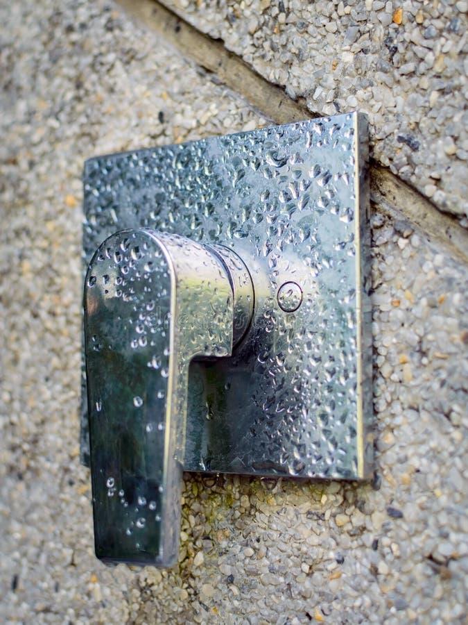 Στρόφιγγα βρυσών ντους στο χρώμιο στον τοίχο πετρών Απελευθερώσεις νερού στο μέταλλο στοκ εικόνες με δικαίωμα ελεύθερης χρήσης