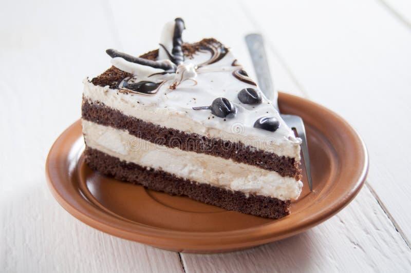 Εύγευστο κέικ Στρώματα του λεπτού κέικ σφουγγαριών κρέμας και σοκολάτας Σε ένα πιάτο κοντά στο δίκρανο Σε ένα άσπρο ξύλινο υπόβαθ στοκ εικόνες