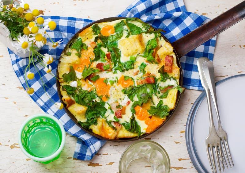 Στρώματα Skillet με το μπέϊκον, το τυρί Cheddar, και τα πράσινα στοκ εικόνες