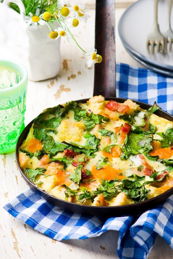 Στρώματα Skillet με το μπέϊκον, το τυρί Cheddar, και τα πράσινα στοκ εικόνα με δικαίωμα ελεύθερης χρήσης