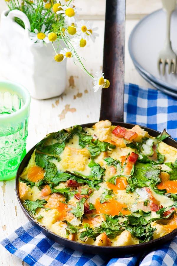 Στρώματα Skillet με το μπέϊκον, το τυρί Cheddar, και τα πράσινα στοκ εικόνες με δικαίωμα ελεύθερης χρήσης