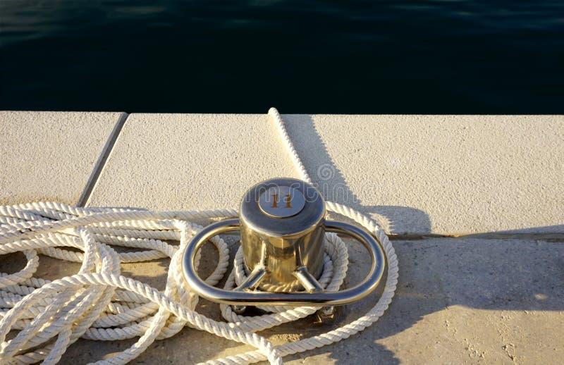 Στυλοβάτης χάλυβα πρόσδεσης με το άσπρο σχοινί βαμβακιού στην αποβάθρα πετρών κοντά στη βαθιά μπλε θάλασσα στοκ φωτογραφία