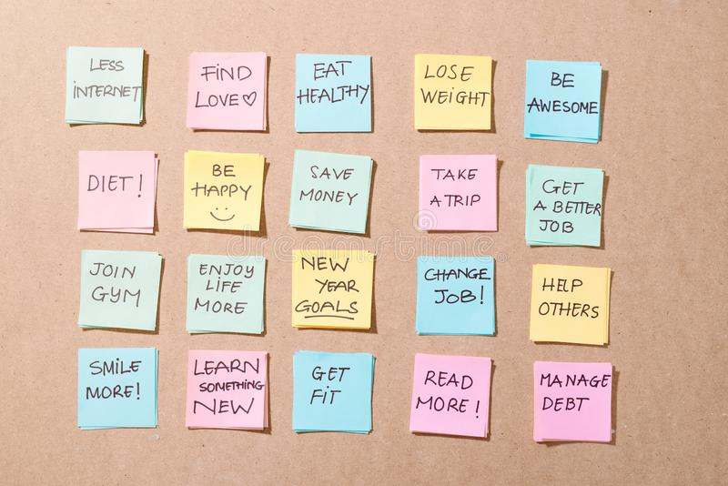 Στόχοι ή ψηφίσματα για το νέο έτος - πολύχρωμα αυτοκόλλητα σημειώματα σε ένα Σημειωματάριο με Κύπελλο Καφέ στοκ φωτογραφίες