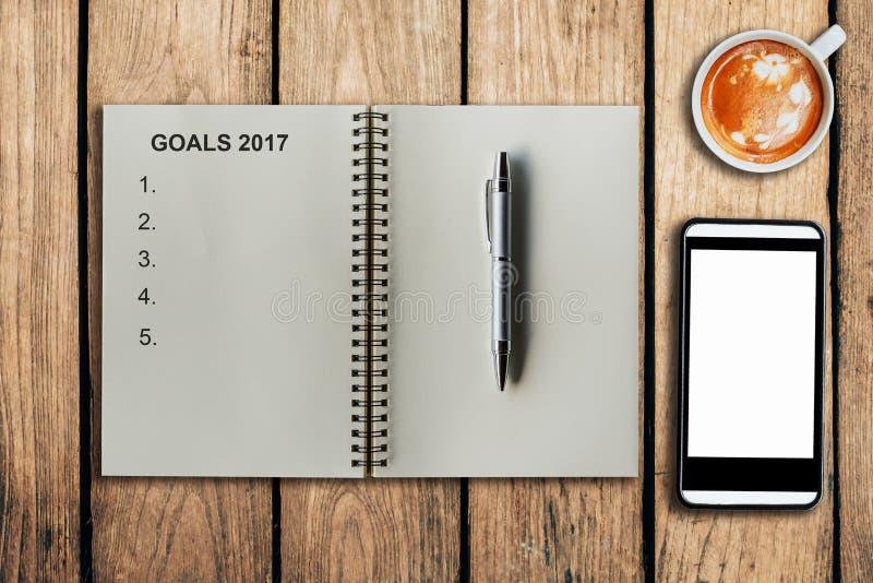 Στόχοι 2017 ως υπόμνημα στο φλυτζάνι σημειωματάριων και καφέ με το κινητό τηλέφωνο στοκ φωτογραφία με δικαίωμα ελεύθερης χρήσης