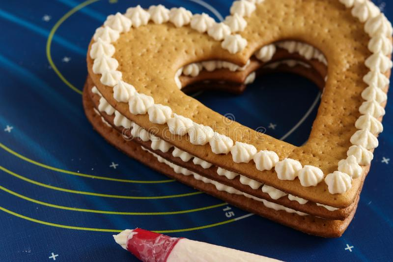 Συγκέντρωση ενός καρδιά-διαμορφωμένου κέικ που χρησιμοποιεί τη βουτύρου κρέμα στοκ φωτογραφία με δικαίωμα ελεύθερης χρήσης