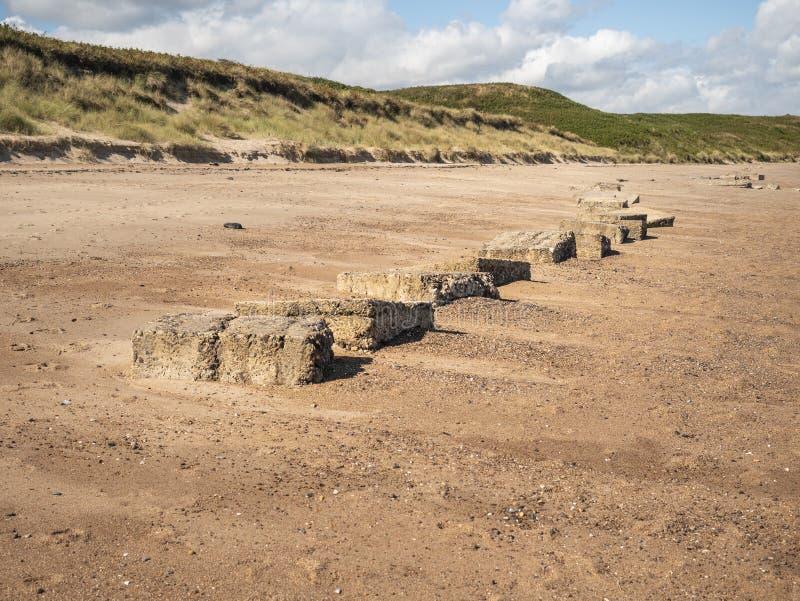 Συγκεκριμένες αντι υπερασπίσεις δεξαμενών που εκτίθενται σε μια παραλία της Northumberland στοκ φωτογραφίες