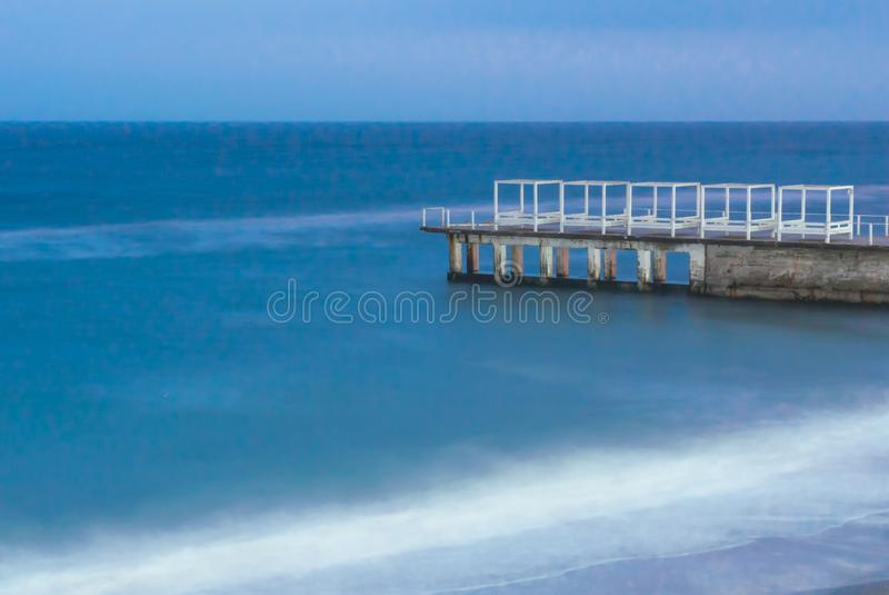 Συγκεκριμένη αποβάθρα, με τα ξύλινα κτήρια σε το, πλυμένος από τα νερά της Μαύρης Θάλασσας Η φωτογραφία λήφθηκε σε μια μακροχρόνι στοκ φωτογραφία