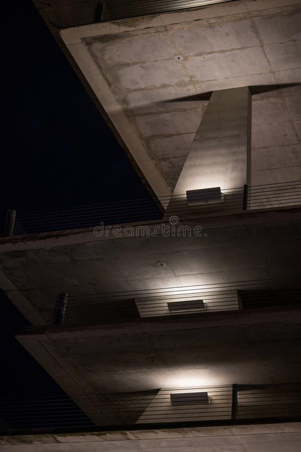 Συγκεκριμένη δομή χώρων στάθμευσης που φωτίζεται τη νύχτα στοκ εικόνες