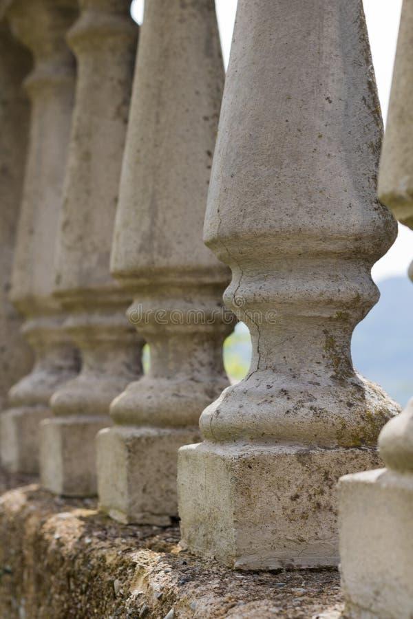 Συγκεκριμένο κιγκλίδωμα με τους κλασσικούς στυλοβάτες που στέκονται σε μια σειρά, που προστατεύει έναν κήπο στην Τοσκάνη στοκ φωτογραφία