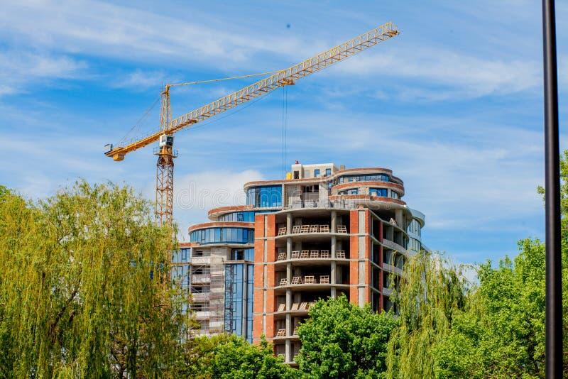 Συγκεκριμένο κτήριο κάτω από την οικοδόμηση Υπόβαθρο εργοτάξιων οικοδομής Γερανός που χτίζει πλησίον στοκ εικόνες