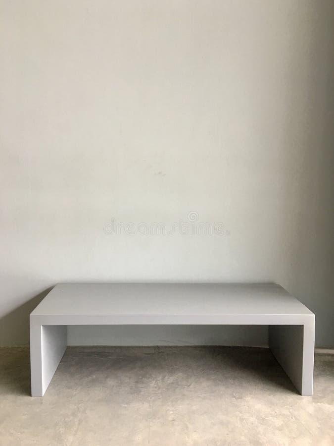 Συγκεκριμένο πιάτο τσιμέντου για το κάθισμα πάγκων μπροστά από τον τοίχο τσιμέντου στοκ εικόνες