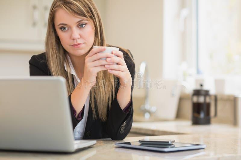 Συγκεντρωμένη γυναίκα που εξετάζει το lap-top με τον καφέ διαθέσιμο στοκ φωτογραφίες