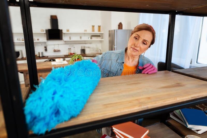 Συγκεντρωμένη γυναίκα που χρησιμοποιεί τον μπλε μεθύστακα panicle παλεύοντας με τη σκόνη στοκ φωτογραφία με δικαίωμα ελεύθερης χρήσης