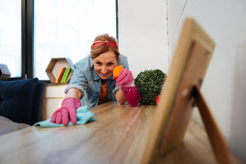 Συγκεντρωμένη ελαφρύς-μαλλιαρή ώριμη γυναίκα που φορά τα ρόδινα λαστιχένια γάντια στοκ εικόνες με δικαίωμα ελεύθερης χρήσης