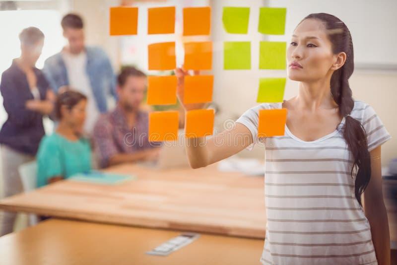 Συγκεντρωμένη επιχειρηματίας που δείχνει τη θέση του επάνω ο τοίχος στοκ εικόνα με δικαίωμα ελεύθερης χρήσης