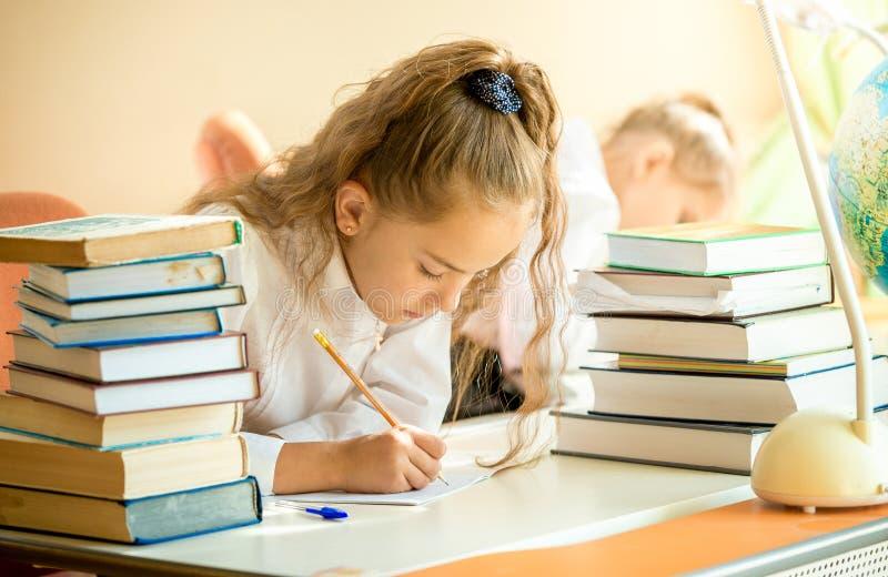 Συγκεντρωμένη μαθήτρια που περιβάλλεται από τα βιβλία που κάνουν την εργασία στοκ εικόνα