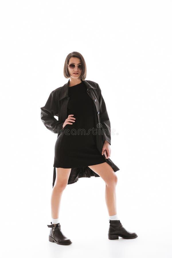 Συγκεντρωμένη νέα κυρία που φορά την τοποθέτηση γυαλιών ηλίου που απομονώνεται στοκ εικόνες