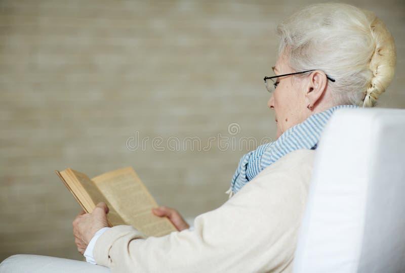 Συγκεντρωμένη συνταξιούχος γυναίκα που διαβάζει το παλαιό βιβλίο στοκ εικόνα με δικαίωμα ελεύθερης χρήσης