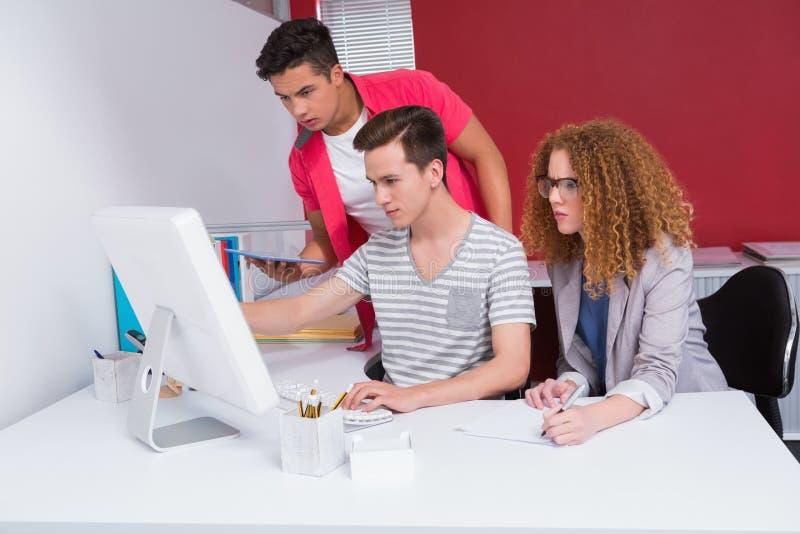 Συγκεντρωμένοι σπουδαστές που χρησιμοποιούν την ταμπλέτα και τον υπολογιστή στοκ φωτογραφίες