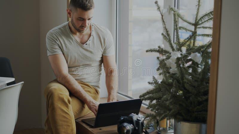 Συγκεντρωμένος αρσενικός φωτογράφος με τη συνεδρίαση καμερών και φορητών προσωπικών υπολογιστών στο windowsill στο σπίτι και μοιρ στοκ εικόνα με δικαίωμα ελεύθερης χρήσης