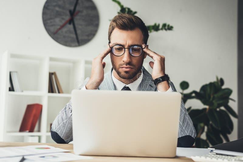 Συγκεντρωμένος επιχειρηματίας με το lap-top στοκ φωτογραφίες