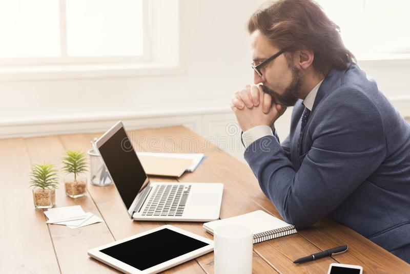 Συγκεντρωμένος επιχειρηματίας που εργάζεται με το lap-top στοκ εικόνα