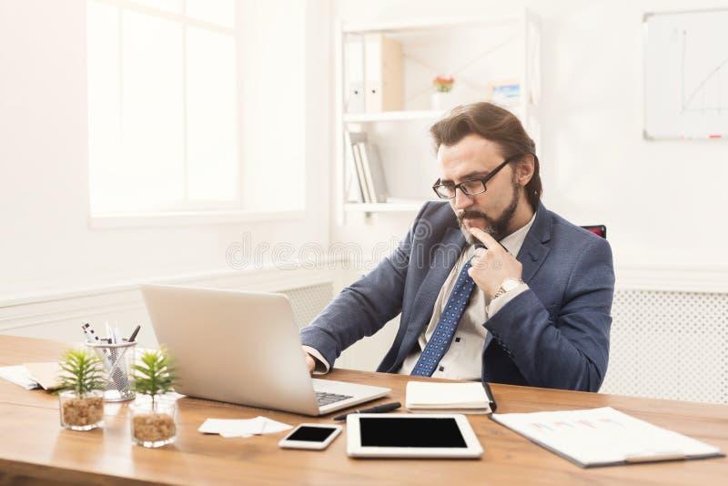 Συγκεντρωμένος επιχειρηματίας που εργάζεται με το lap-top στοκ φωτογραφίες