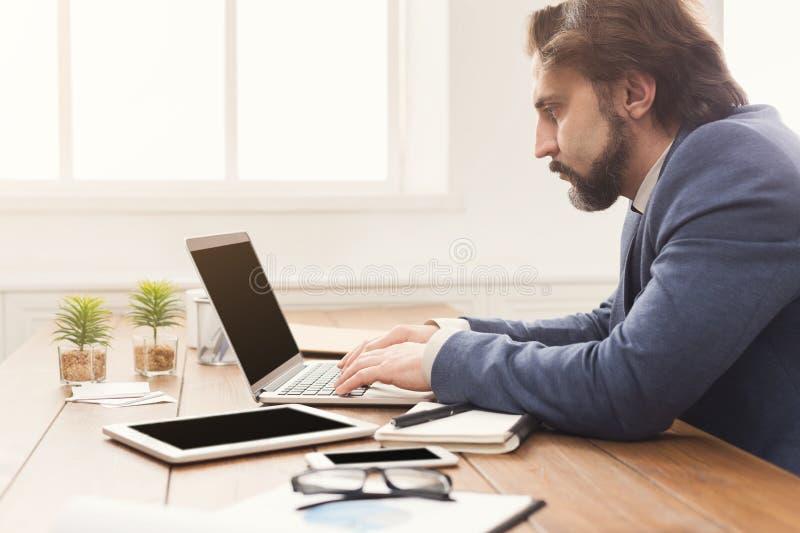 Συγκεντρωμένος επιχειρηματίας που εργάζεται με το lap-top στοκ φωτογραφίες με δικαίωμα ελεύθερης χρήσης