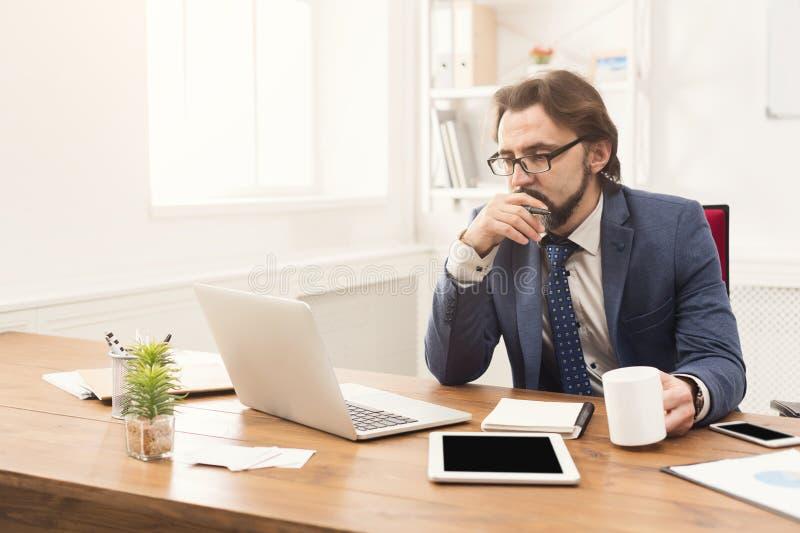 Συγκεντρωμένος επιχειρηματίας που εργάζεται με το lap-top στοκ εικόνα με δικαίωμα ελεύθερης χρήσης