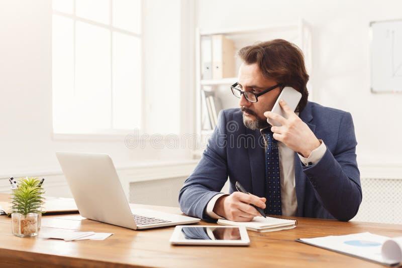 Συγκεντρωμένος επιχειρηματίας που μιλά στο κινητό τηλέφωνο στοκ φωτογραφίες με δικαίωμα ελεύθερης χρήσης