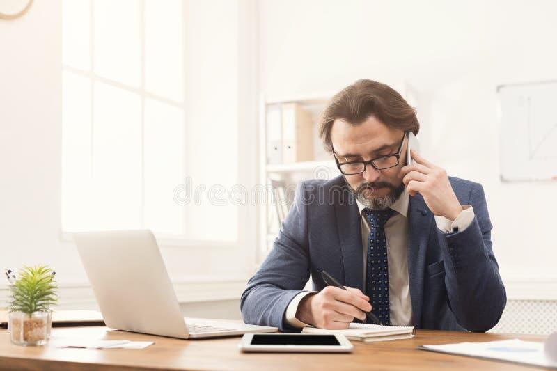 Συγκεντρωμένος επιχειρηματίας που μιλά στο κινητό τηλέφωνο στοκ φωτογραφία