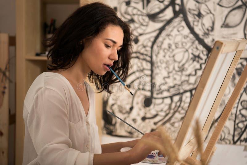 Συγκεντρωμένος θηλυκός καλλιτέχνης που σύρει την εικόνα στο studior της στοκ φωτογραφία
