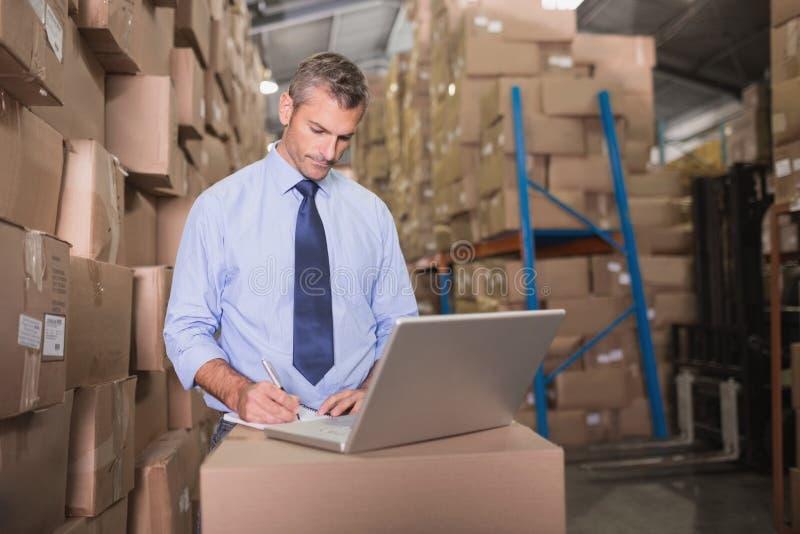Συγκεντρωμένος διευθυντής αποθηκών εμπορευμάτων που χρησιμοποιεί το lap-top στοκ φωτογραφία με δικαίωμα ελεύθερης χρήσης