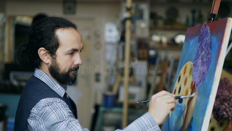 Συγκεντρωμένος καλλιτέχνης ατόμων που χρωματίζει ακόμα την εικόνα ζωής στον καμβά στο στούντιο τέχνης στο εσωτερικό στοκ εικόνες