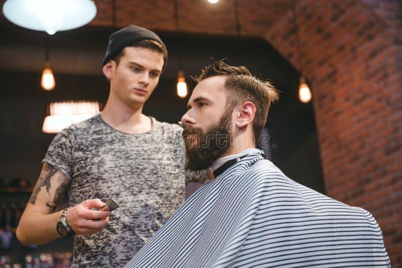 Συγκεντρωμένος κομμωτής που κάνει το κούρεμα στο γενειοφόρο όμορφο άτομο στο barbershop στοκ εικόνα