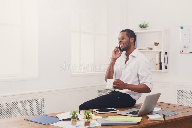 Συγκεντρωμένος μαύρος επιχειρηματίας στο σύγχρονο γραφείο, εργασία με την ταμπλέτα στοκ εικόνες