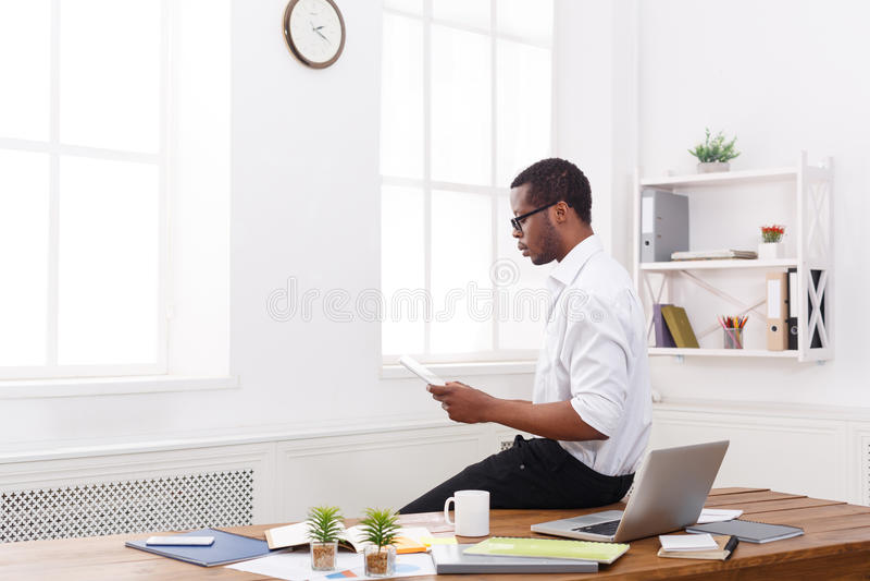 Συγκεντρωμένος μαύρος επιχειρηματίας στο σύγχρονο γραφείο, εργασία με την ταμπλέτα στοκ φωτογραφία με δικαίωμα ελεύθερης χρήσης